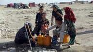Internally displaced Afghans, who fled their home due to fighting between the Taliban and Afghan security personnel, fill water…