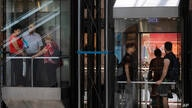 People ride an elevators at a shopping mall after restrictions requiring face masks indoors was lifted, in Tel Aviv, Tuesday,…