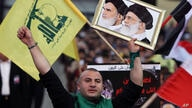 A Hezbollah supporter chants slogans, as he holds a picture of the late Iran revolutionary founder Ayatollah Khomeini, left,…