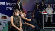 Israeli President Isaac Herzog speaks to his wife, Michal, left, before the couple received a third coronavirus vaccine at the…