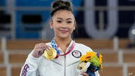 Gold medalist Sunisa Lee of the United States displays her medal for the artistic gymnastics women's all-around at the 2020…