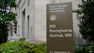 FILE - This May 4, 2021 file photo shows a sign outside the Robert F. Kennedy Department of Justice building in Washington. The…
