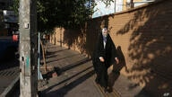 A woman wearing protective face mask to help prevent the spread of the coronavirus walks on a sidewalk in southern Tehran, Iran…