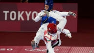 Iran's Nahid Kiyani, front, attacks Kimia Alizadeh, of the Refugee Olympic Team, during the women's 57kg match at the 2020…
