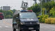 A police vehicle with equipment mounted on top patrols outside the Tianjin Binhai No. 1 Hotel where U.S. and Chinese officials…