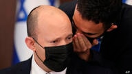 Israeli Prime Minister Naftali Bennett is spoken to as he attends a cabinet meeting at the prime minister's office in Jerusalem…
