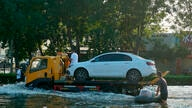 A tow truck drives along a flooded street in Xinxiang in central China's Henan Province, Monday, July 26, 2021. Forecasters…