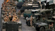 Lebanese army soldiers sit on their vehicles as they deployed to contain the tension after heavy fire in the coastal town of…
