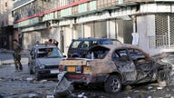 An Afghan national army soldier, left, stands guard near debris following an attack in Kabul, Afghanistan, Wednesday, Aug. 4,…