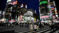 People walk along a pedestrian crossing Friday, July 30, 2021, in Tokyo, as Japanese Prime Minister Yoshihide Suga expanded a…