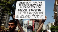 An anti-government protester holds a placard during a protest marking the first anniversary of the massive blast at Beirut's…