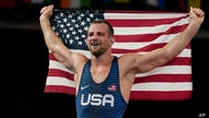 United States' David Morris Taylor III celebrates holding the US flag after winning the gold medal in the men's 86kg Freestyle…