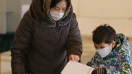 A woman and a child cast a ballot during a presidential election and constitutional referendum in Bishkek