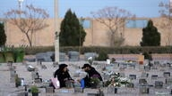 An Iranian couple sit in a cemetery, where dead people and coronavirus disease (COVID-19) victims are buried, in south of Tehran