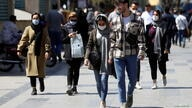 Iranian people wear protective face masks, as they walk amid the spread of the coronavirus disease (COVID-19), in Tehran