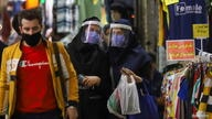 Iranian women wear protective face shields and masks as they walk in Tehran Bazaar in Tehran