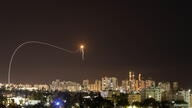 A streak of light is seen as Israel's Iron Dome anti-missile system intercepts rockets launched from the Gaza Strip towards Israel, as seen from Ashkelon, Israel