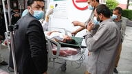People transport an injured woman to a hospital after a blast in Kabul