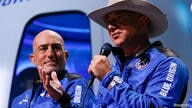 Billionaire American businessman Jeff Bezos speaks with his brother Mark at a post-launch press conference, in the nearby town of Van Horn