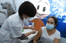 A healthcare worker administers a COVID-19 vaccine to an Israeli woman at Clalit Health Services, in the coastal city of Tel…