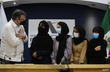 The Mexican Secretary of Foreign Affairs Marcelo Ebrard (L) welcomes four Afghan women, members of the Afghanistan Robotic team…
