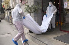 Forensic workers carry a body from a hotel downtown Bucharest, Romania, Friday, June 19, 2020. Gholamreza Mansouri, a former…