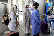 A health worker, right, checks temperature of passengers to help prevent the spread of the coronavirus upon arrival at the…