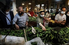 People wearing face masks to help prevent the spread of the coronavirus shop at the old grand bazaar of the city of Zanjan,…