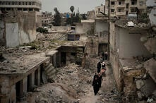 In this Thursday, March 12, 2020 photo, women walk in a neighborhood heavily damaged by airstrikes in Idlib, Syria. Idlib city…