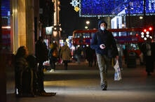 A man wears a face mask as he walks past a man begging for alms in the normally busy Oxford Street in central London, Tuesday,…