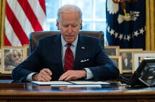 President Joe Biden signs a series of executive orders on health care, in the Oval Office of the White House, Thursday, Jan. 28…