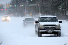 Vehicles drive on snow and sleet covered roads Monday, Feb. 15, 2021, in Spring, Texas. A winter storm dropping snow and ice…