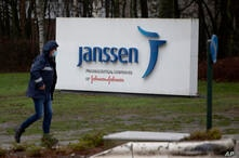 A man walks by a sign outside Johnson & Johnson subsidiary, Janssen Pharmaceutical, in Geel, Belgium, Wednesday, Feb. 3, 2021…
