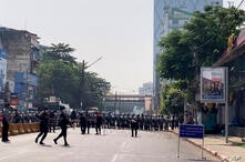 In this image made from video, a row of riot police blocks the road to prevent protesters from marching forward Saturday, Feb…