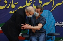 Health Minister Saeed Namaki, left, tries to the kiss hand of Dr. Fattah Ghazi as a sign of respect, after he received a…
