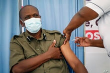A police officer has his blood pressure taken before receiving a shot of the AstraZeneca COVID-19 vaccine, manufactured by the…