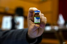 An Iranian official holds a vial of an Iranian-made
