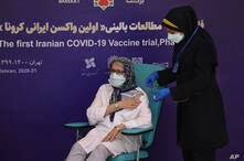 The supervisor of the Coviran Barekat Covid-19 vaccine research team, Dr. Monoo Mohraz, left, receives the vaccine during the…
