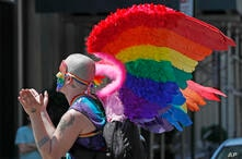A man wearin rainbow wings and a rainbow colored mask claps as he participates in a queer liberation march for Black Lives…