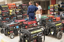 Generator salesman Ahmed Muhammad, 22, right, talks with a customer at his shop in central Baghdad, Iraq on Saturday, Aug. 4,…