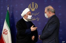 In this photo released by the official website of the office of the Iranian Presidency, President Hassan Rouhani, left, talks…