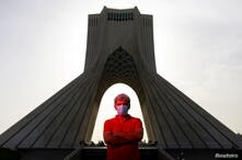 Iranian man Rouzbeh, 21, poses for a photo in front of Azadi tower in Tehran
