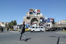 A man walks along a street decorated with posters depicting Syria's President Bashar al-Assad in Damascus
