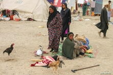 A family arrive from Afghanistan into Pakistan, are seen with their belongings as they taking refuge near a railway station in Chaman,