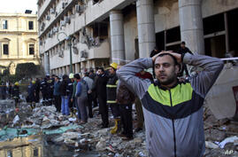An Egyptian man stands in rubble after an explosion at the Egyptian police headquarters in downtown Cairo. Three bombings hit high-profile areas around Cairo on Friday, including a suicide car bomber who struck the city's police headquarters.