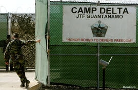 A U.S. Army soldier closes the gate at maximum security prison Camp Delta at Guantanamo Naval Base August 25, 2004 in Guantanamo, Cuba. Australian al Qaeda suspect David Hicks sat stoically before a U.S. military tribunal that formally charged him with wa