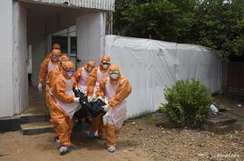 FILE - Members of a burial team, wearing protective suits, remove a body from an Ebola holding center at the Port Loko District Hospital in Sierra Leone Sept. 27, 2014.