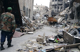 A Free Syrian Army fighter carries his weapon as he walks along a damaged street in Aleppo's Khan al-Wazeer district, Syria, December 16, 2012.