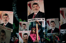 "Supporters of Egypt's ousted President Mohamed Morsi posters with Arabic writing which reads ""Yes for legality, No for the coup"" during a protest outside Rabaah al-Adawiya mosque, Cairo, August 6, 2013."
