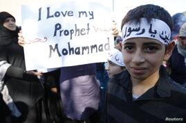 Muslim children hold up a placard before taking part in a protest march against a U.S-made film and cartoons published by a French magazine that denigrate Islam's Prophet Mohammad, in Freiburg September 21, 2012.     REUTERS/Vincent Kessler (GERMANY  - Ta